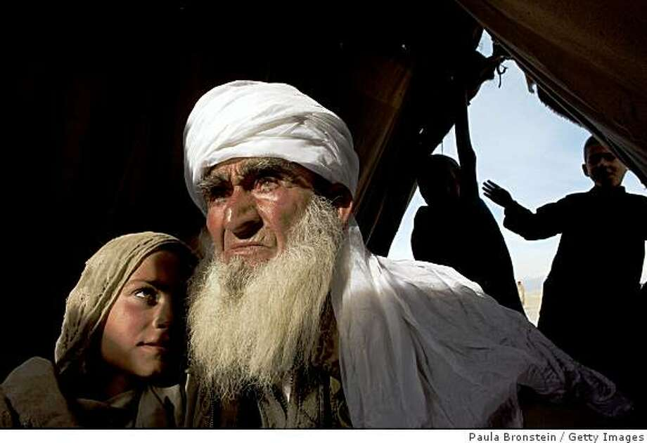 LAGHMAN, AFGHANISTAN - FEBRUARY 08:  Sayed Abdul Karim, 80-years-old, sits with his grandaughter, Camina, 9-years-old, (L) in an internally displaced camp three hours from their village in Galochi district, bombed in a recent US military raid February 08, 2009 in Laghman, Afghanistan. The operation drove hundreds of families out of their villages after 270 homes were destroyed and 16 civilians killed. President Karzai condemned the raid stating that it only weakened the Afghan government and strengthened the terrorists. The operation resulted in the deaths of only 15 militants. Civilian causualties at the hand of foreign troops have become a sensitive issue in a country where the anger amongst the locals creates huge tensions between the Karzai goverment and the foreign troops. The families of the region say they have been attacked six times and are still not receiving no assistance.  (Photo by Paula Bronstein/Getty Images) Photo: Paula Bronstein, Getty Images