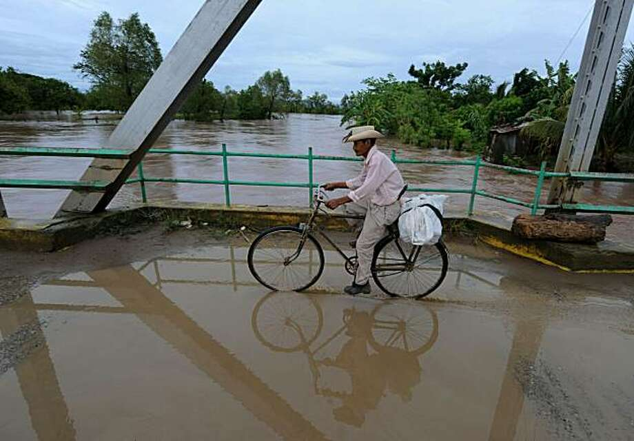 A peasant crosses a bridge over the overflooded Ulua river, after the passage of Tropical Storm Matthew in the municipality El Progreso, department of Yoro, 265 km north of Tegucigalpa, on September 25, 2010. Tropical Storm Matthew drenched Central America Saturday with torrential rain, forcing thousands to evacuate and bringing fresh misery to a region where hundreds have died in flooding and landslides this year. Photo: Orlando Sierra, AFP/Getty Images