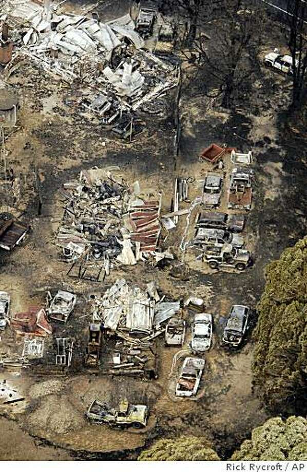 Buildings and vehicles sit destroyed at Kinglake northeast of Melbourne, Australia, Sunday, Feb. 8, 2009. Towering flames have razed entire towns in southeastern Australia and burned fleeing residents in their cars as the death toll rose to 84, making it the country's deadliest fire disaster. At least 700 homes were destroyed in Saturday's inferno. (AP Photo/Rick Rycroft) Photo: Rick Rycroft, AP