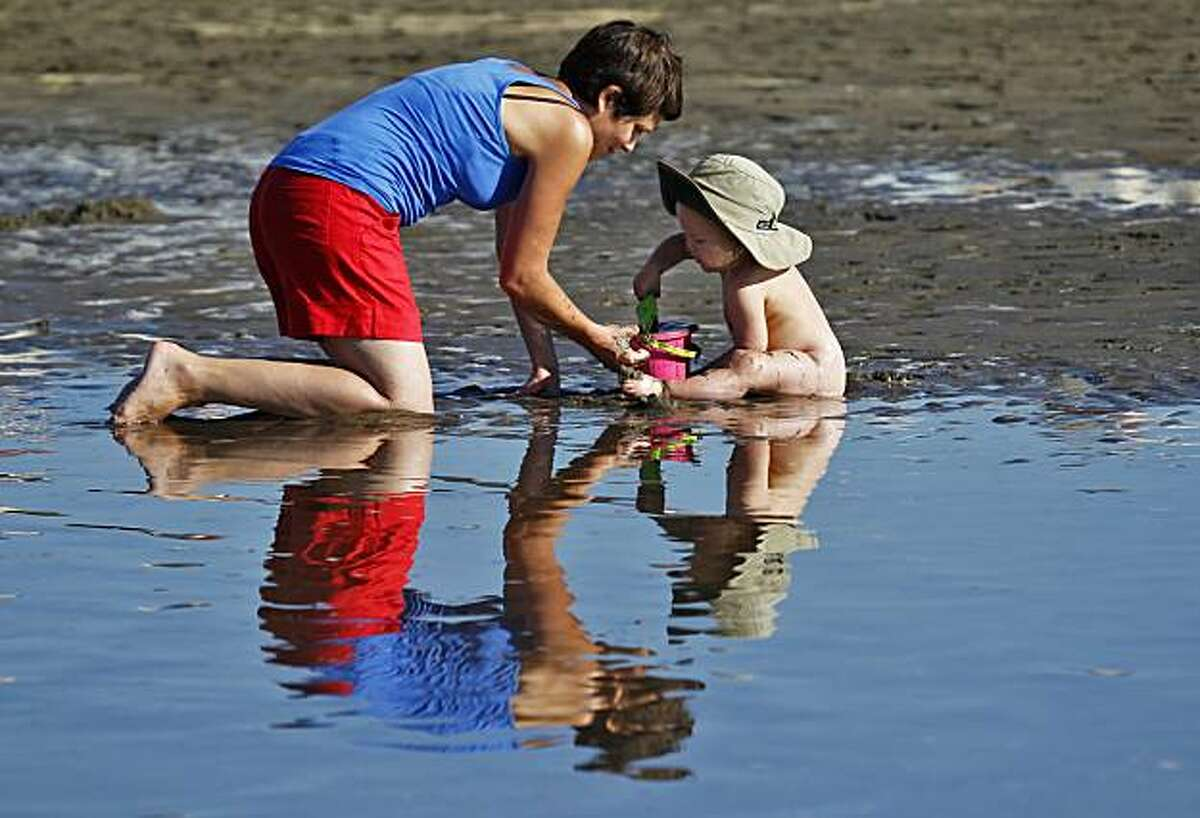 Kitty Agnoli helps her daughter Anna Etsu, 20 months, build a mud pie as they cool down Monday at Ocean Beach in San Francisco.
