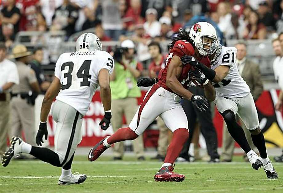 Runningback Larry Fitzgerald #11 of the Arizona Cardinals runs with the football after a reception against Nnamdi Asomugha #21 and Mike Mitchell #34 of the Oakland Raiders during the third quarter of the NFL game at the University of Phoenix Stadium on September 26, 2010 in Glendale, Arizona.  The Cardinals defeated the Raiders 24-23. Photo: Christian Petersen, Getty Images