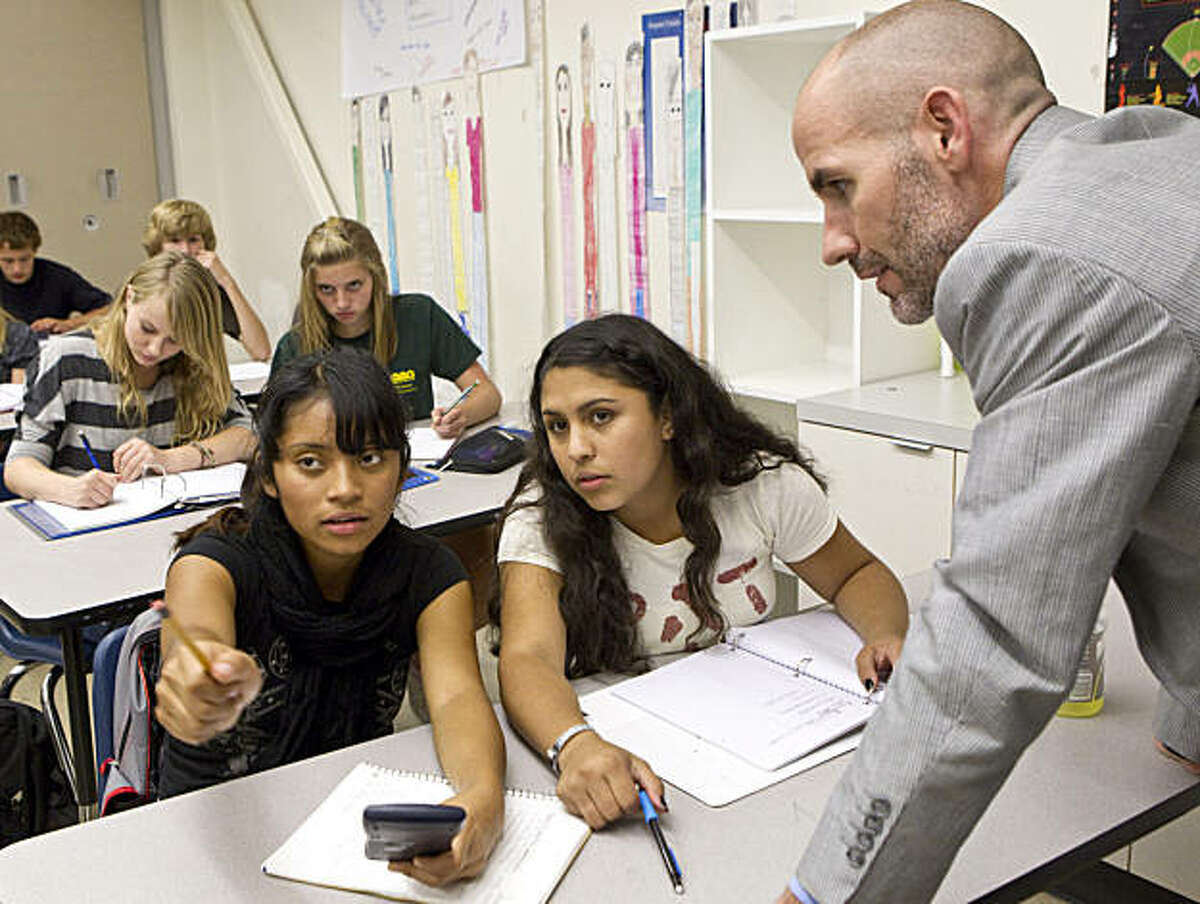 Summit Preparatory Charter High School Executive Director Todd Dickson helps Arleni Barrios (left) and Adriana Corrales while observing their science class at the school in Redwood City, Calif., on Friday, September 24, 2010.