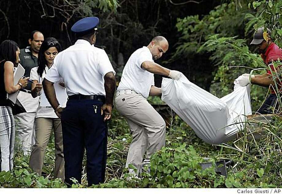 Forensic personnel remove the body of Sara Kuszak, who lived in Savannah, Ga., from a field in Ceiba, eastern Puerto Rico, Wednesday, Feb. 4, 2009. Kuszak, a pregnant tourist, was abducted Wednesday and stuffed into the trunk of a car, where she made a desperate call for help on her cell phone. Her body was later found with its throat slashed and police arrested a local man whose clothing was splattered with blood. (AP Photo/Carlos Giusti, Primera Hora.com)  **  NO SALES  ** Photo: Carlos Giusti, AP