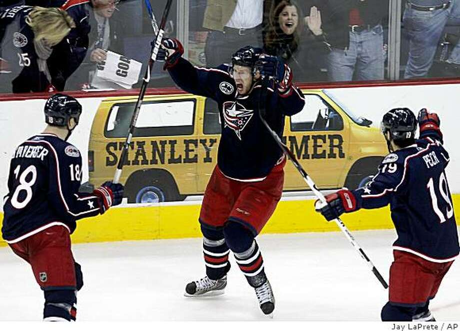 Columbus Blue Jackets' Christian Backman, center, of Sweden, celebrates his game-winning goal against the San Jose Sharks with teammates R.J. Umberger, left, and Michael Peca during the overtime period of an NHL hockey game Saturday, Feb. 7, 2009, in Columbus, Ohio. The Blue Jackets defeated the Sharks 3-2. (AP Photo/Jay LaPrete) Photo: Jay LaPrete, AP