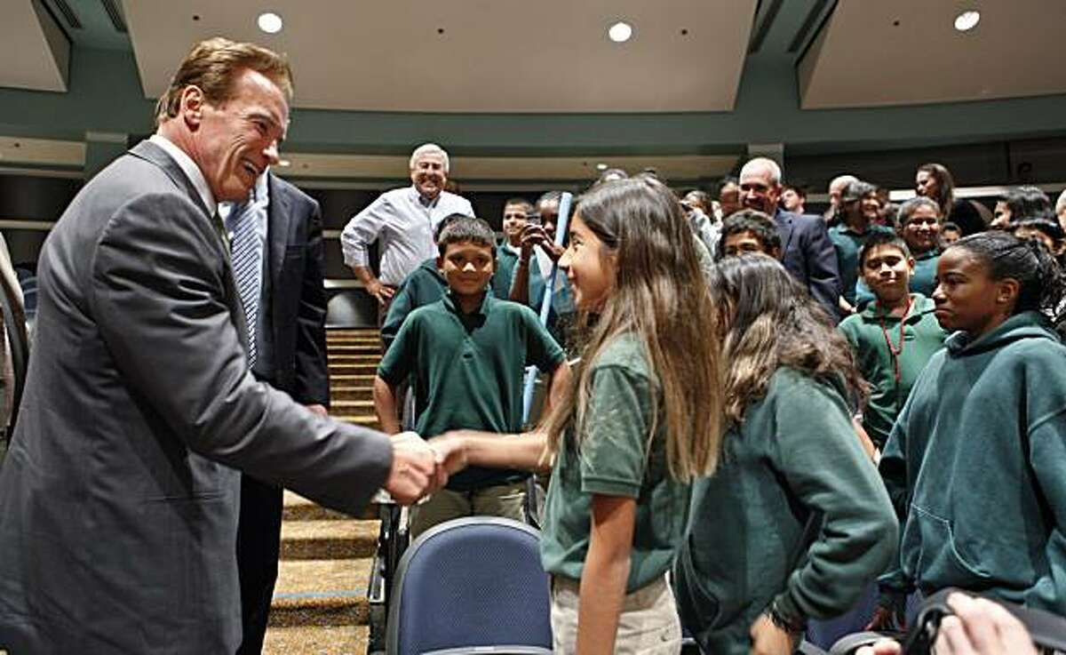Gov. Arnold Schwarzenegger, left, shakes hands with students from Beechwood School in Menlo Park, Calif., after he spoke at the Commonwealth Club in Santa Clara, Calif., Monday, Sept. 27, 2010. Schwarzenegger is blasting the oil companies that are tryingto undermine California's global warming law, saying they are motivated purely by greed.
