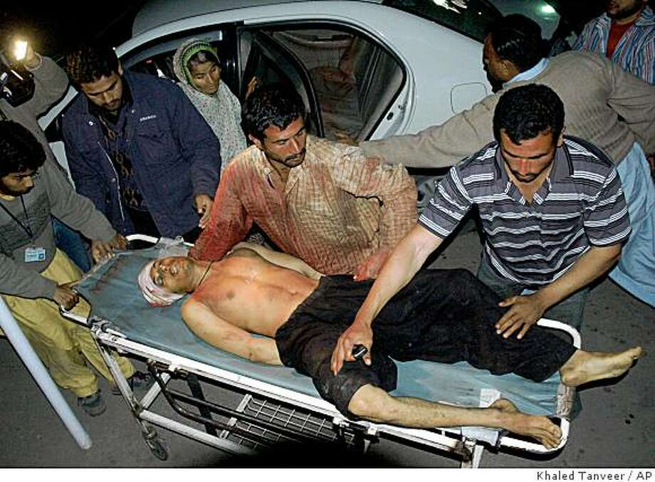 A wounded Pakistani man is carried on a stretcher after an explosion in Dera Ghazi Khan, at a local hospital in Multan, Pakistan, Thursday, Feb. 5, 2009. A suicide bomber blew himself up among worshippers streaming toward a Shiite Muslim mosque in central Pakistan on Thursday, killing 24 people and wounding dozens more. (AP Photo/Khalid Tanveer) Photo: Khaled Tanveer, AP