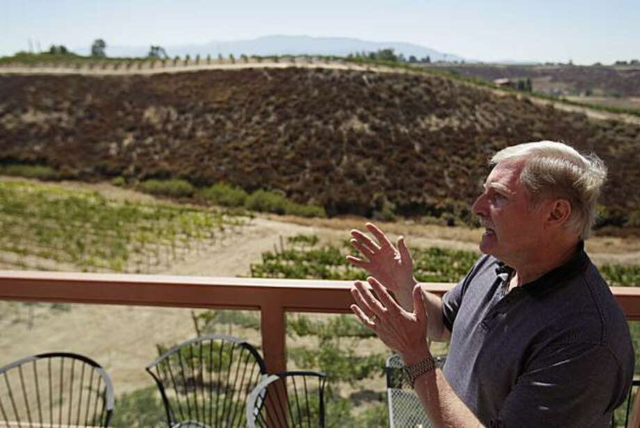 In this Sept. 17, 2010 photo, Ray Falkner, of the Falkner Winery, speaks in front of a hilltop, behind, that has been bought by the Calvary Chapel Bible Fellowship in Temecula, Calif. Some Temecula wineries are battling a local church with plans to expand, which they say could negatively affect their wine producing region. Photo: Gregory Bull, AP