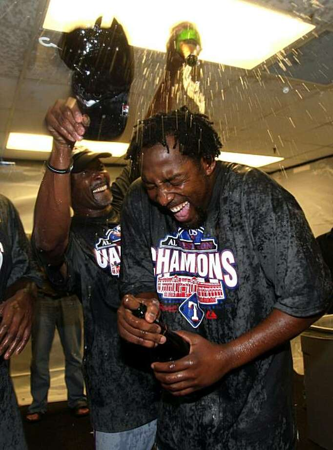 OAKLAND, CA - SEPTEMBER 25:  Vladimir Guerrero #27 of the Texas Rangers is covered in champagne by Gary Pettis after they beat the Oakland Athletics to clinch the American League West Title at the Oakland-Alameda County Coliseum on September 25, 2010 in Oakland, California. Photo: Ezra Shaw, Getty Images