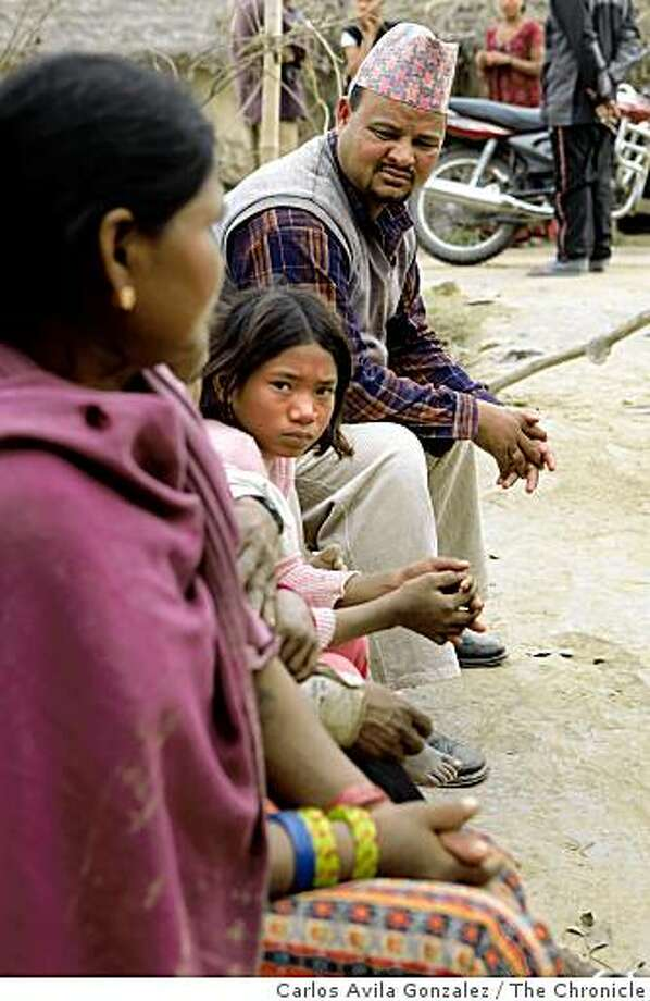 Naresh Bahadur Shasi, a clothing store owner, tries to make a deal with the parents of Kausi Chaudhary, 10, seated center, to renew his contract to keep her as a kamlari, or domestic slave for another year. Photo: Carlos Avila Gonzalez, The Chronicle