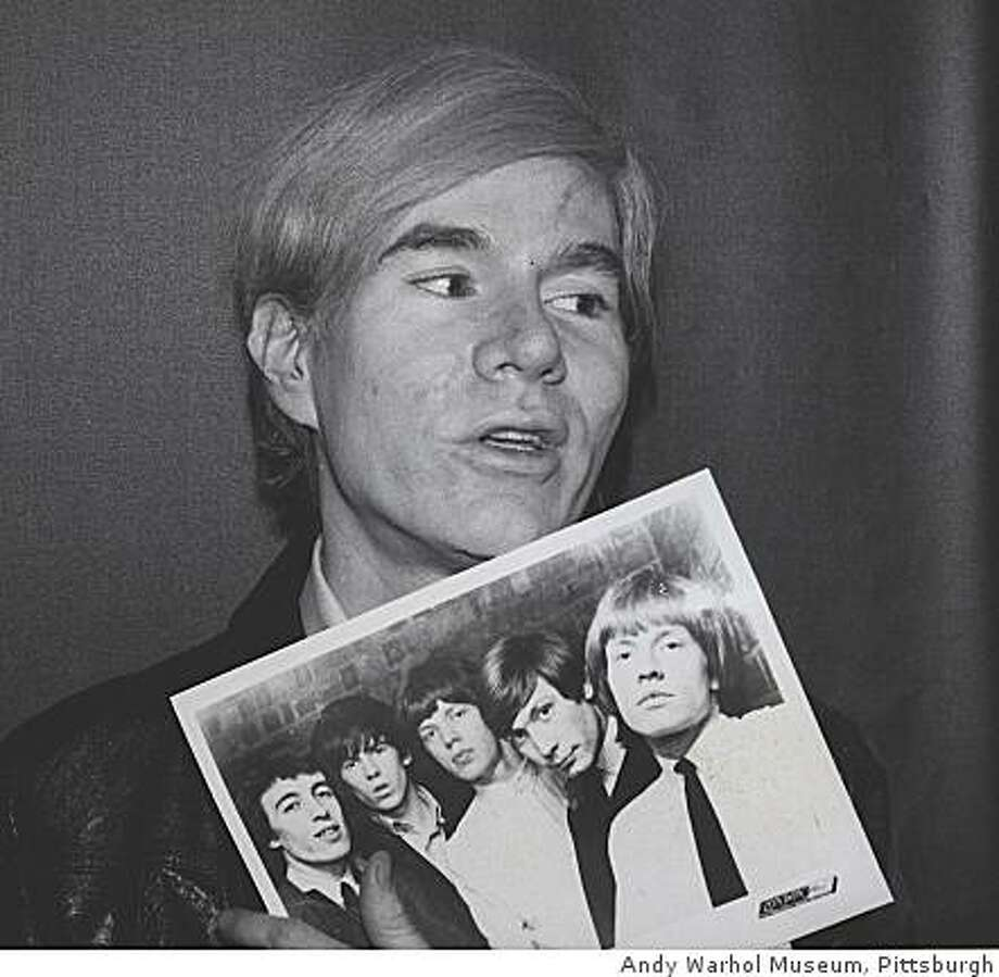 Andy Warhol holding a 1964 publicity photo of the Rolling Stones in 1969 (Founding Collection, Andy Warhol Foundation for the Visual Arts Inc.) Photo: Andy Warhol Museum, Pittsburgh