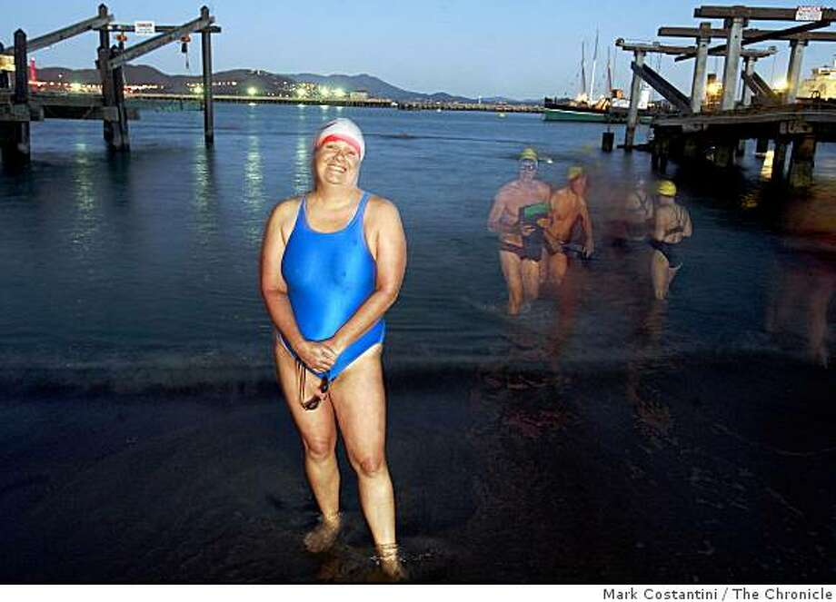 In the dark, before sunrise, when she practices, Suzie Dods, 48, an open water swimmer stands at the water's edge at the Dolphin Club in San Francisco, Calif. Behind her are other swimmers leaving the water after they are finished practicing. Photo: Mark Costantini, The Chronicle