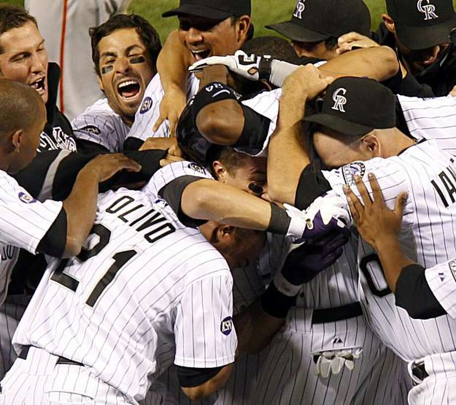 Colorado Rockies Troy Tulowitzki, center, is congratulated by teammates after his walk off hit in the 10th inning drove in the winning run against the San Francisco Giants in a baseball game at Coors Field in Denver on Saturday, Sept. 25, 2010. The Rockies defeated the Giants 10-9. Photo: Ed Andrieski, AP