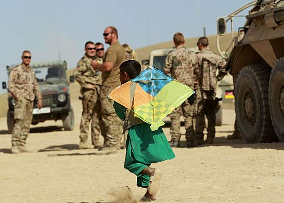 MAZAR-E-SHARIF, AFGHANISTAN - SEPTEMBER 25: A boy with a kite walks past  German Bundeswehr soldiers near  Camp Marmal on September 25, 2010 in Mazar-e-Sharif, Afghanistan. Germany has more than 4,500 military forces in Afghanistan as part of the US-led International Security Assistance Force. (Photo by Miguel Villagran/Getty Images) *** BEST PIX *** Photo: Miguel Villagran, Getty Images