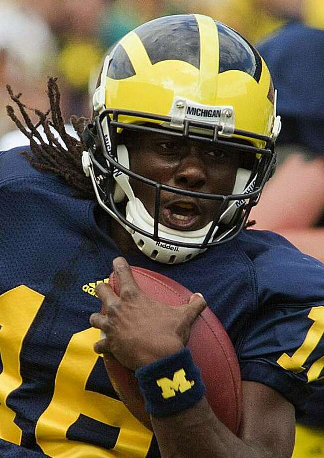 "FILE - In this Sept. 4, 2010, file phot, Michigan quarterback Denard Robinson (16) rushes past Connecticut linebacker Scott Lutrus during  the first quarter of an NCAA college football game in Ann Arbor, Mich. Coach Herbert O. ""Fritz"" Crisler came up with the idea of the ""winged"" helmet when he came to Michigan from Princeton 1938 so the Wolverines' receivers would standout down field. Little did he know that it would still look awesome more than 70 years later. (AP Photo/Tony Ding, File Photo: Tony Ding, AP"