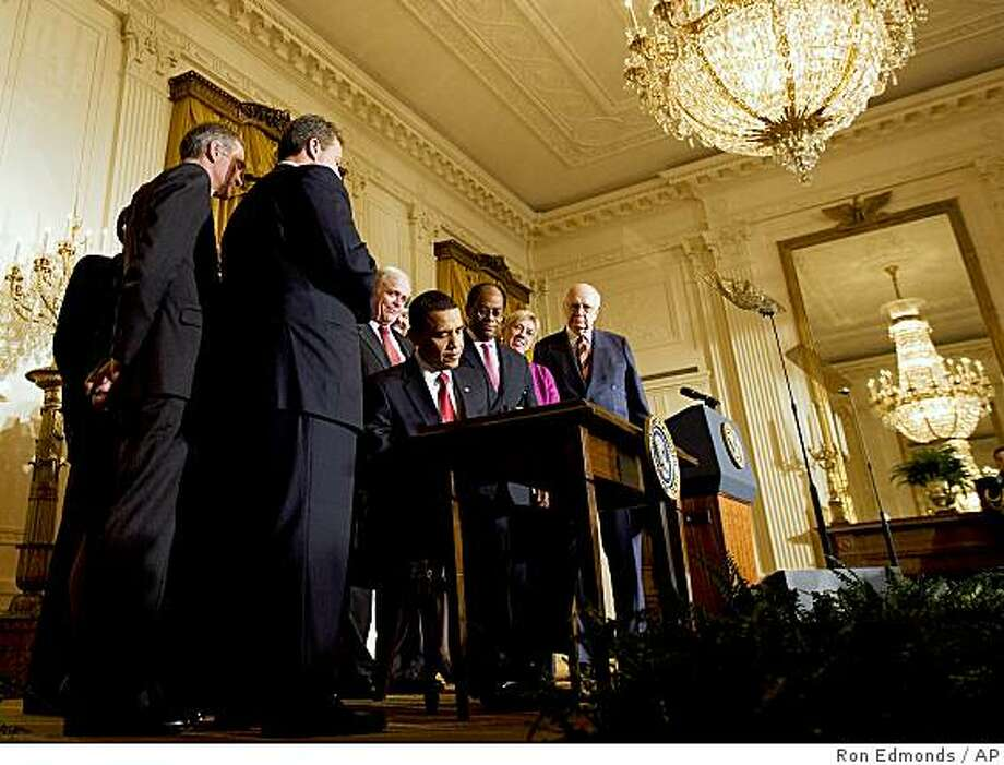 President Barack Obama, surrounded by members of the President's Economic Recovery Advisory Board, signs an executive order forming the board, Friday, Feb. 6, 2009, in the East Room of the White House in Washington.     (AP Photo/Ron Edmonds) Photo: Ron Edmonds, AP