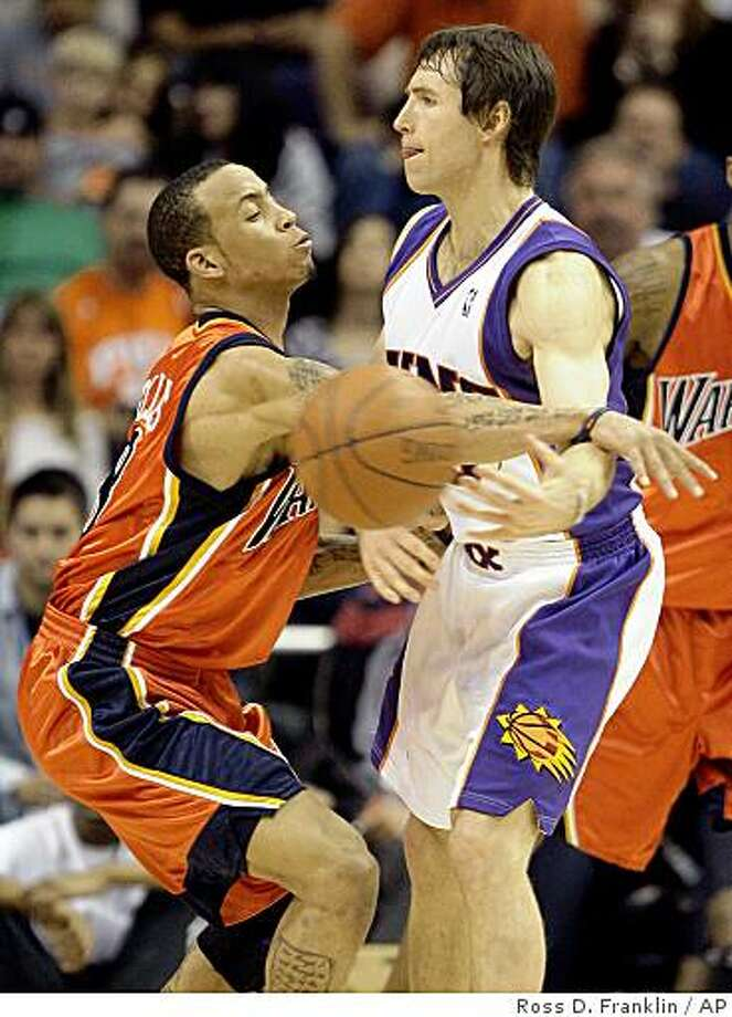 Phoenix Suns' Steve Nash, right, passes the ball around Golden State Warriors Monta Ellis in the first quarter of an NBA basketball game Friday, Feb. 6, 2009, in Phoenix. (AP Photo/Ross D. Franklin) Photo: Ross D. Franklin, AP