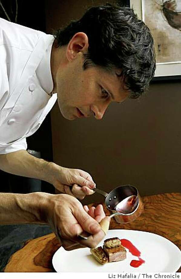 Chef Daniel Patterson of Coi prepares a duck breast sous vide in foie gras fat, with sauteed foie gras and hibiscus sauce. Photo: Liz Hafalia, The Chronicle