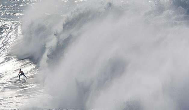 A surfer races in front of crashing waves during the finals of the Mavericks Surf Contest in Half Moon Bay, Calif. on Saturday, Feb. 13, 2010. Photo: Adam Lau, The Chronicle