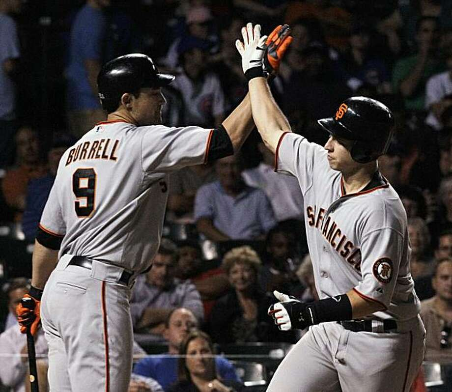 San Francisco Giants' Buster Posey, right, celebrates with Pat Burrell after his home run off Chicago Cubs relief pitcher Andrew Cashner during the eighth inning of a baseball game Tuesday, Sept. 21, 2010, at Wrigley Field in Chicago. Photo: Charles Rex Arbogast, AP
