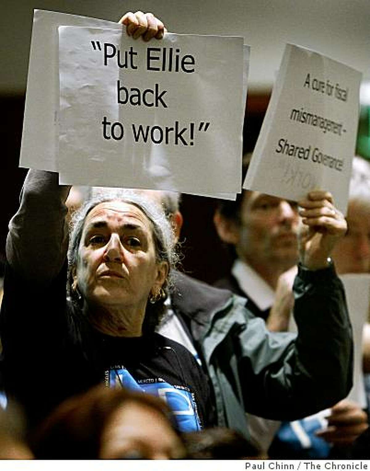 Kathy Ann Miller holds a sign in support of Ellie Corley, a UC Berkeley employee who's being laid off after 33 years, during the UC Regents meeting at the UCSF Mission Bay campus in San Francisco, Calif., on Wednesday, Feb. 4, 2009.