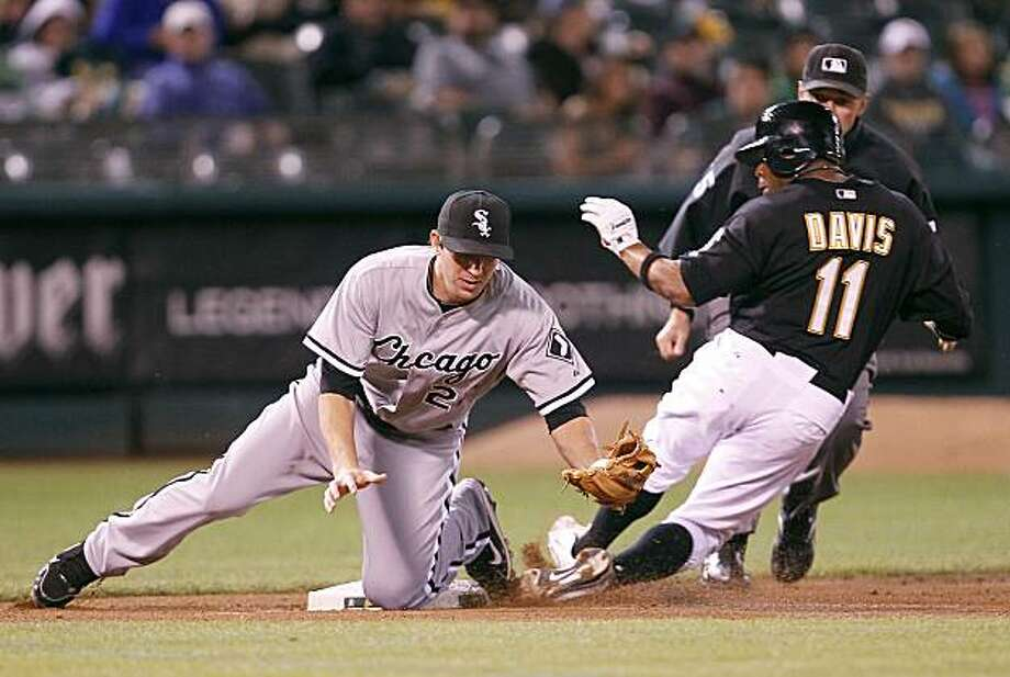 Oakland Athletics Rajai Davis (11) beats the tag of Chicago White Sox third baseman Brent Morel as he steals third base during the third inning of a baseball game Monday, Sept. 20, 2010, in Oakland, Calif. Photo: Tony Avelar, AP