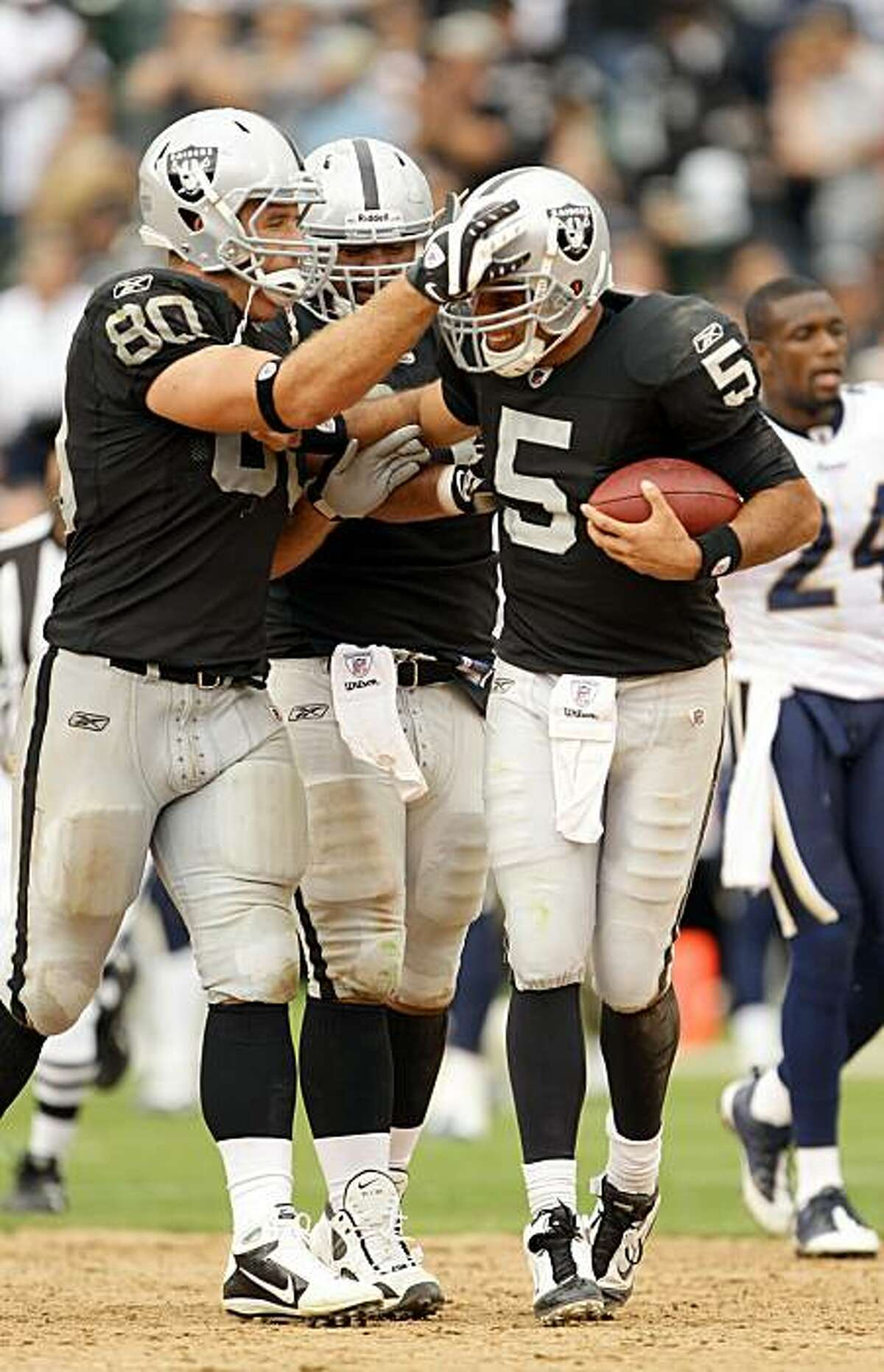 OAKLAND, CA - SEPTEMBER 19: Bruce Gradkowski #5 of the Oakland Raiders is congratulated by Zach Miller #80 after they beat the St. Louis Rams at the Oakland-Alameda County Coliseum on September 19, 2010 in Oakland, California.