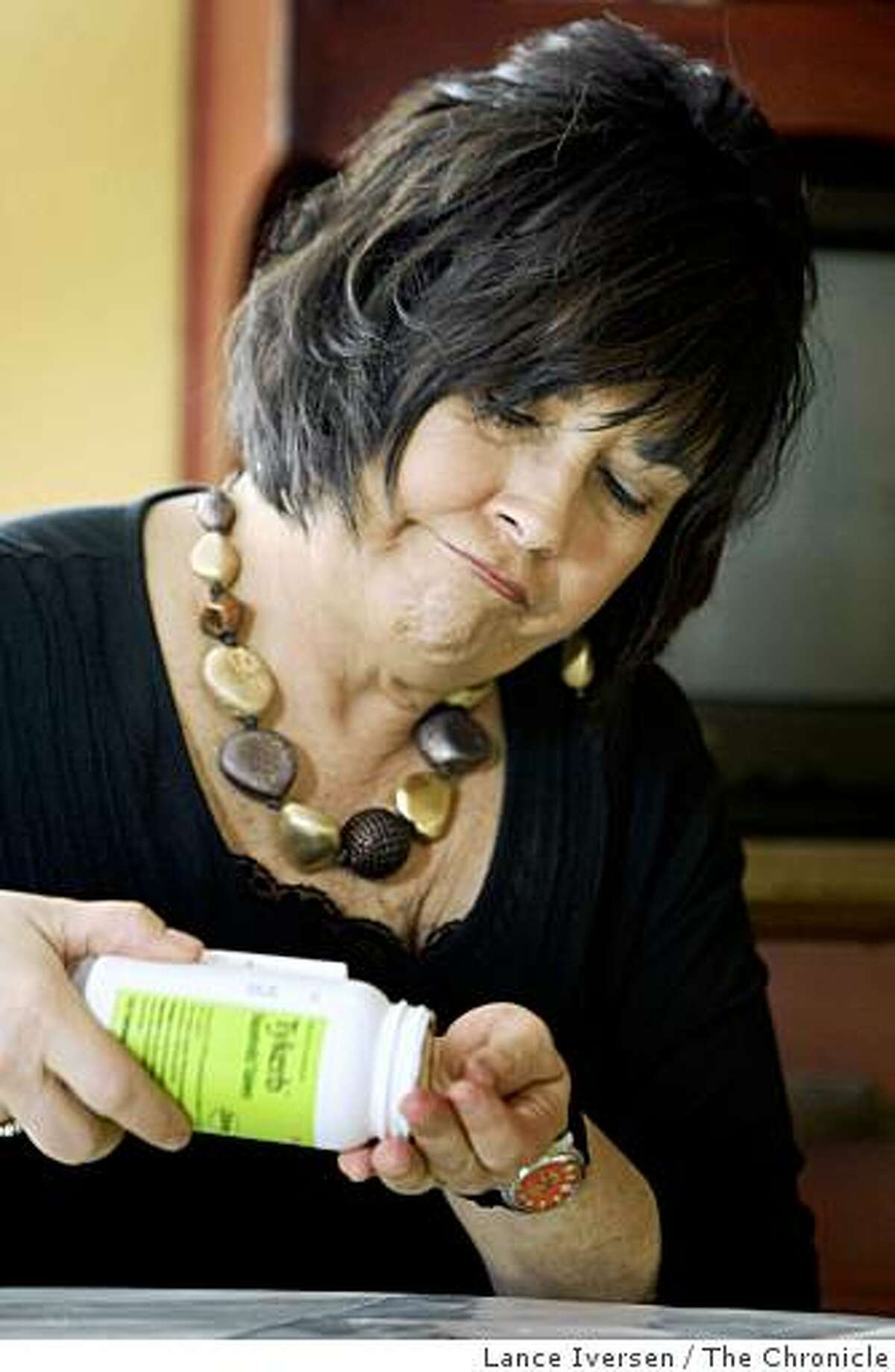 Christine Franklin, a cancer survivor, shows some of the medication she has to take in Vacaville, Calif., on Feb. 4, 2009.