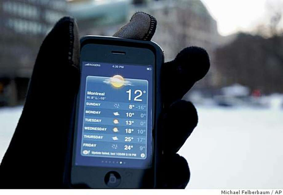 A person wearing Tavo gloves holds an iPhone 3G in Montreal, Canada, Sunday, Jan. 26, 2009. The $40 gloves, equipped with electronically conductive tips on the index finger and thumb of each hand, allow touch screen junkies to answer their phone, text and send e-mails in cold weather. (AP Photo/Michael Felberbaum) Photo: Michael Felberbaum, AP