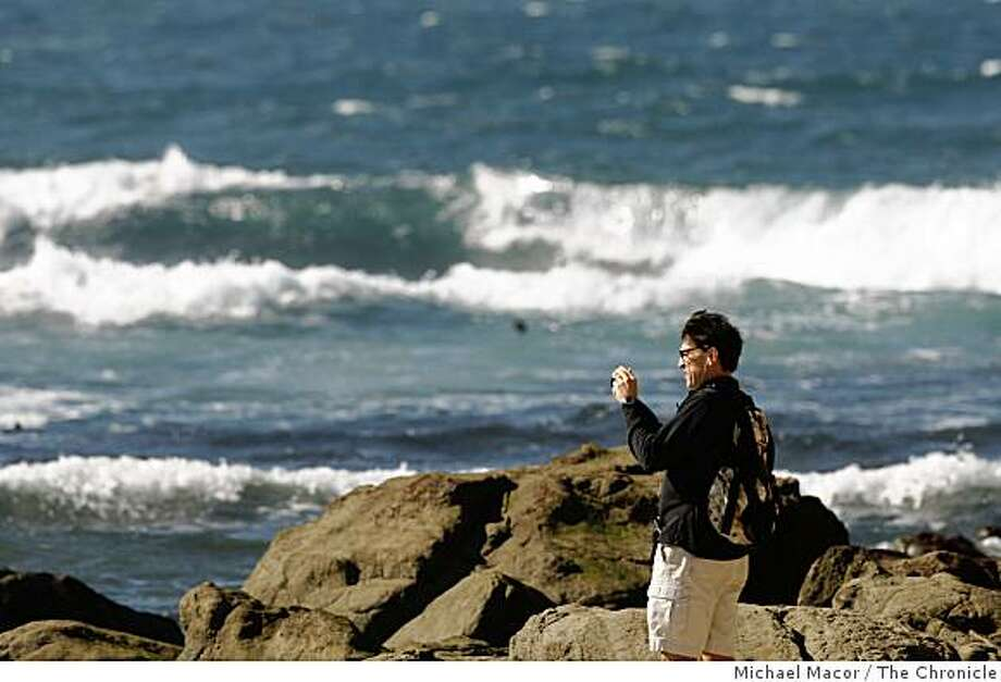 Warren Murray, of Half Moon Bay, photographs the waters out toward Maverick's break as fairly calm seas moves towards the shore at Half Moon Bay, Calif., on Saturday Jan. 31, 2008. Photo: Michael Macor, The Chronicle