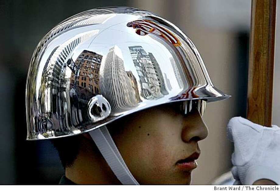 The tall buildings of San Francisco were reflected in the helmet of Phelan Guan, who has been with the Lowell High School ROTC program for two years. He held an American flag as he marched down Market Street. Photo: Brant Ward, The Chronicle