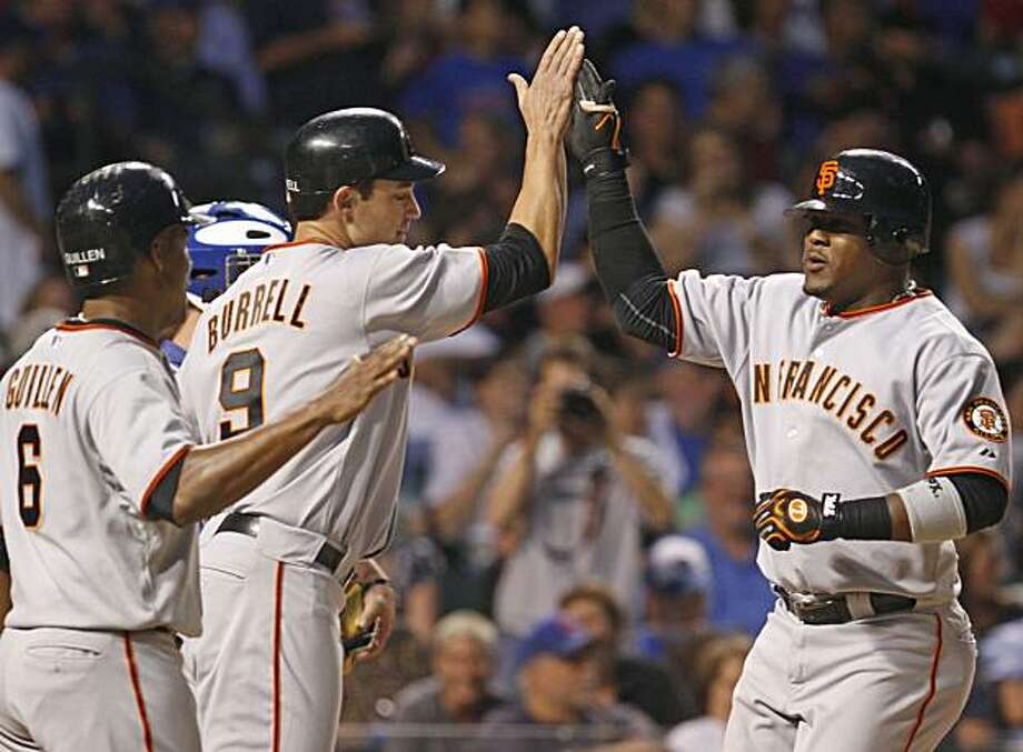 San Francisco Giants' Juan Uribe, right, celebrates with teammates Pat Burrell, center, and Jose Guillen after hitting a grand slam during the second inning of a baseball game against the Chicago Cubs, Thursday, Sept. 23, 2010, in Chicago. Uribe also hita two-home run in the inning. Photo: Nam Y. Huh, AP