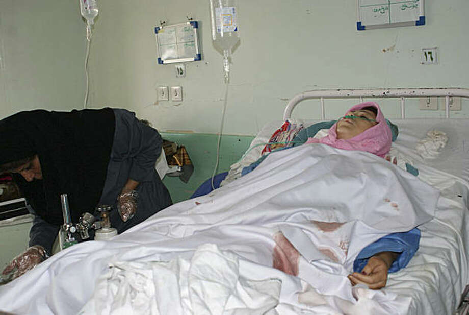 A female medic treats a female victim of a bomb blast, who lies injured in a hospital at the city of Mahabad, northwestern Iran, Wednesday, Sept. 22, 2010. A bomb exploded at a military parade in northwestern Iran on Wednesday, killing 10 spectators in anattack that one official blamed on Kurdish separatists who have fought Iranian forces in the area for decades. Photo: Rahim Bayazidi, AP