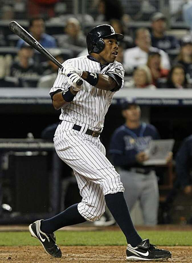 New York Yankees' Curtis Granderson watches his sixth-inning, three-run home run off Tampa Bay Rays reliever Grant Balfour in a baseball game at Yankee Stadium in New York, Monday, Sept. 20, 2010. Photo: Kathy Willens, AP