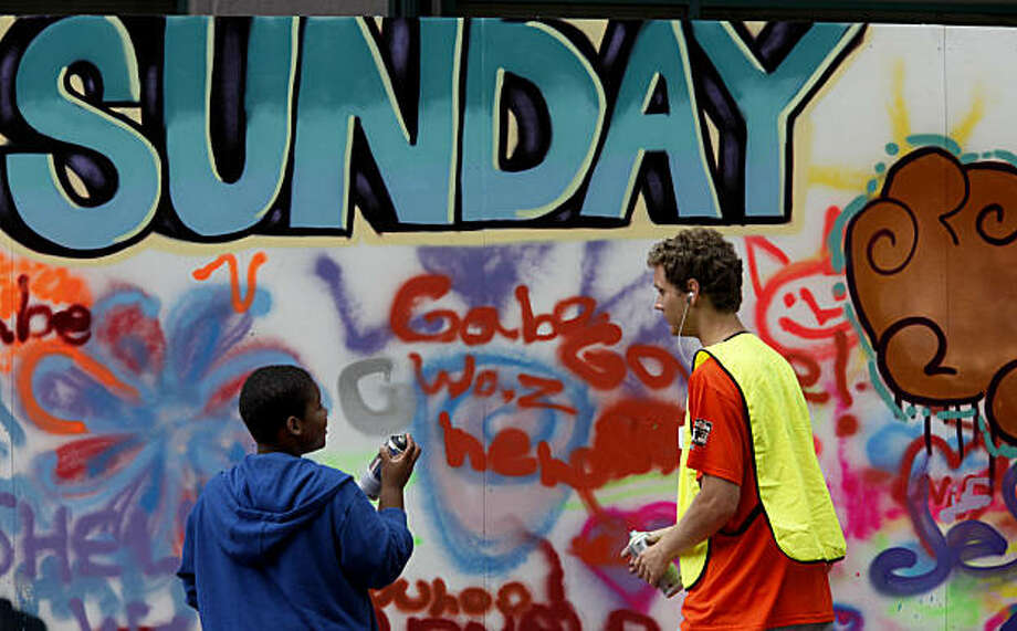 Darrell Wilson (left), 10, gets some help with his graffiti from Dylan Dingle on Fillmore Street at Sunday Streets in San Francisco's Western Addition. Photo: Brant Ward, The Chronicle