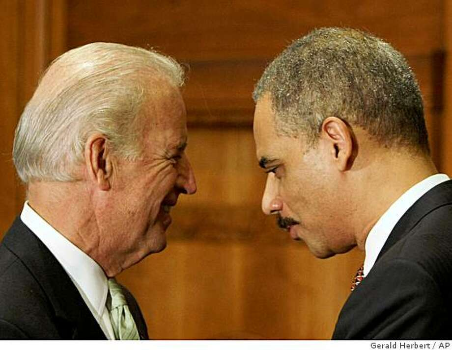 Vice President Joseph Biden huddles with Attorney General Eric Holder after Holder's swearing in ceremony, Tuesday, Feb. 3, 2009, at the Justice Department in Washington. (AP Photo/Gerald Herbert) Photo: Gerald Herbert, AP