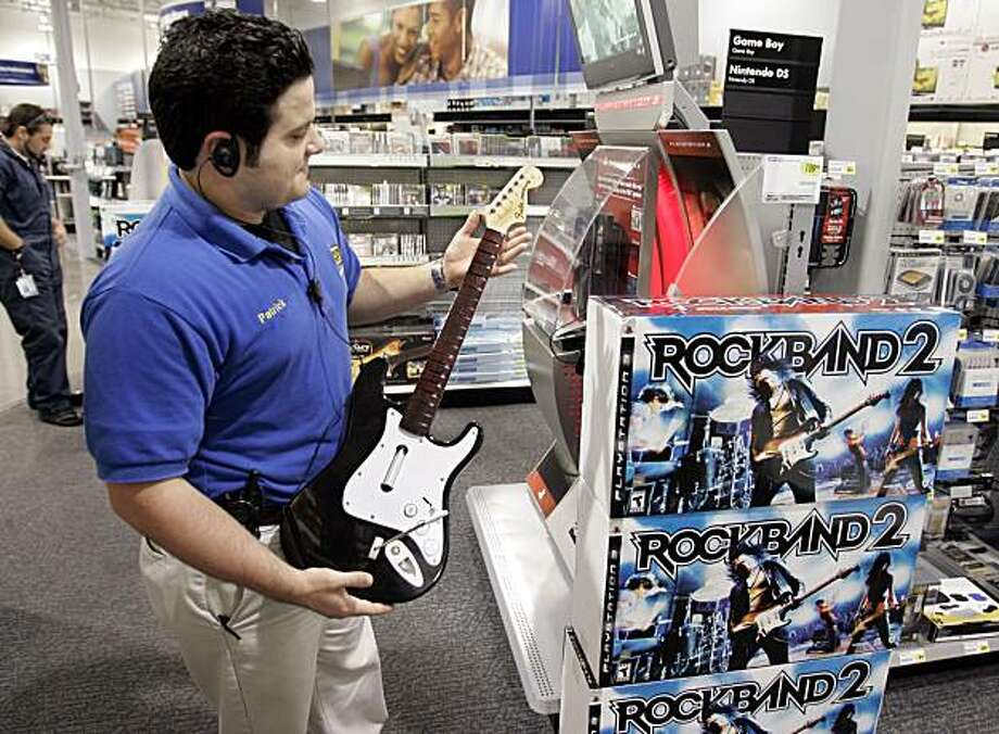 "** FILE ** In this Nov. 19, 2008 file photo, a worker holds up a guitar as part of the ""Rock Band 2"" special edition video game bundle for the PlayStation at Best Buy in Mountain View, Calif.  Hurt by weak holiday sales and a slew of charges, video game publisher Electronic Arts Inc. posted a wider net loss for its fiscal third quarter and fell short of analysts' expectations Tuesday, Feb. 3, 2009.  (AP Photo/Paul Sakuma, file) Photo: Paul Sakuma, AP"