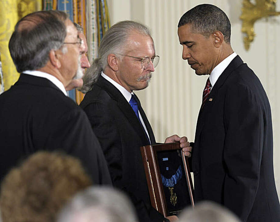 President Barack Obama presents the Medal of Honor posthumously to the sons of Air Force Chief Master Sgt. Richard L. Etchberger, from right, Richard Etchberger, Corey Etchberger, and step son Steve Wilson , Tuesday, Sept. 21, 2010, during a ceremony in the East Room of the White House in Washington. Etchberger received the honor for his heroic actions in combat in Laos on March 11, 1968, after deliberately exposing himself to enemy fire in order to put his wounded comrades in rescue slings permitting them to be airlifted to safety. Photo: Susan Walsh, AP