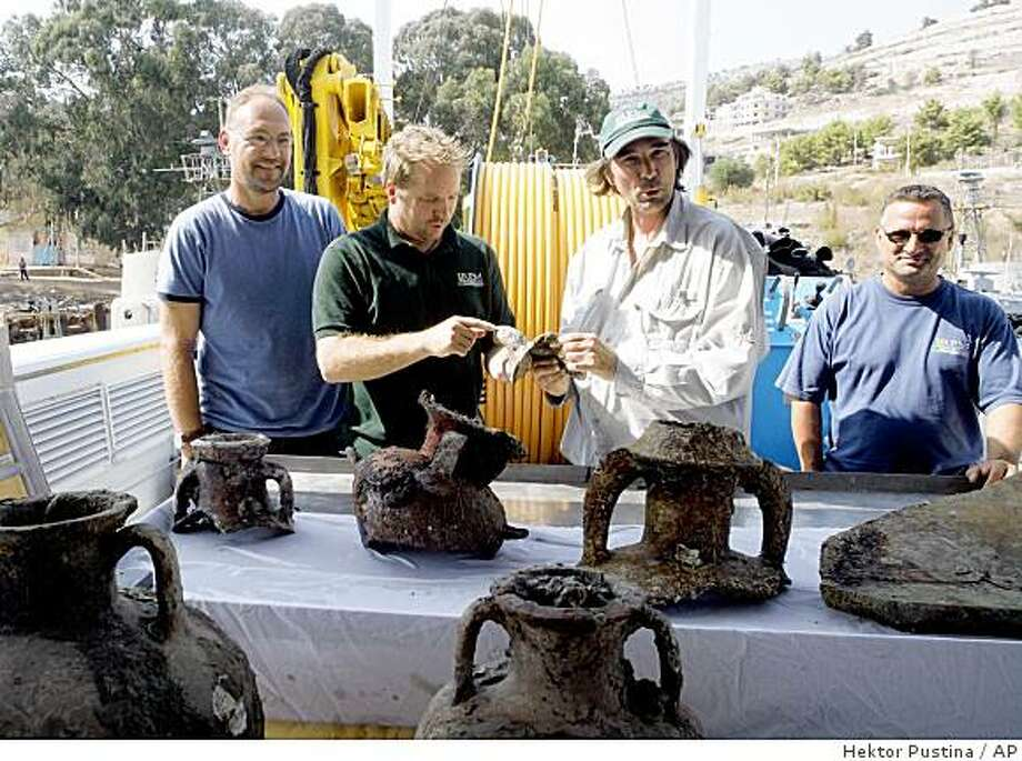 **APN ADVANCE FOR SUNDAY FEB.1**   Albanian mission coordinator Auron Tare, left, U.S. archaeologist Jeffrey G. Royal, second from left, mission leader George Robb, second from right, and archaeologist Adrian Anastas, right, of the Key West, Fla-based RPM Nautical Foundation, a nonprofit group leading the underwater survey, pose with a table of amphora and other objects found in the Ionian seabed, in Saranda, 300 kilometers (186 miles) south of Tirana, Albania, Monday, Aug. 25, 2008. (AP Photo/Hektor Pustina) Photo: Hektor Pustina, AP