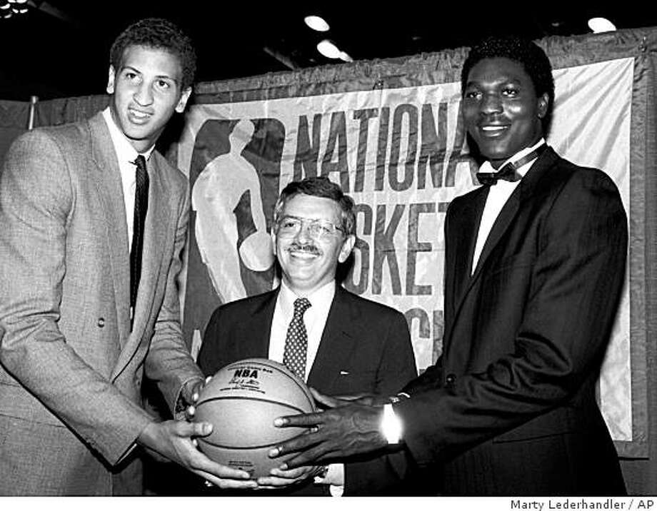 ** ADVANCE FOR WEEKEND EDITIONS JAN. 31-FEB. 1 **  FILE ** In this June 19, 1984 file photo, NBA commissioner David Stern, center, is flanked by Akeem Olajuwon, right, the No. 1 pick overall by the Houston Rockets, and Sam Bowie, the No. 2 pick overall by the Portland Trail Blazers at the NBA Draft in New York. After 25 years of taking the NBA around the globe, David Stern still isn't ready to stay at home. Not when so many challenges remain, so many new opportunities exist to grow the sport. (AP Photo/Marty Lederhandler, File) Photo: Marty Lederhandler, AP