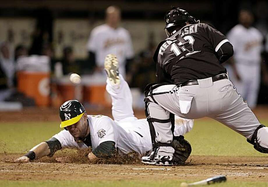 Oakland Athletics' Daric Barton, left, slides to score as Chicago White Sox catcher A.J. Pierzynski (12) misses the catch at home plate during the third inning of a baseball game Tuesday, Sept. 21, 2010, in Oakland, Calif. Barton scored on a double by Kurt Suzuki. Photo: Ben Margot, AP