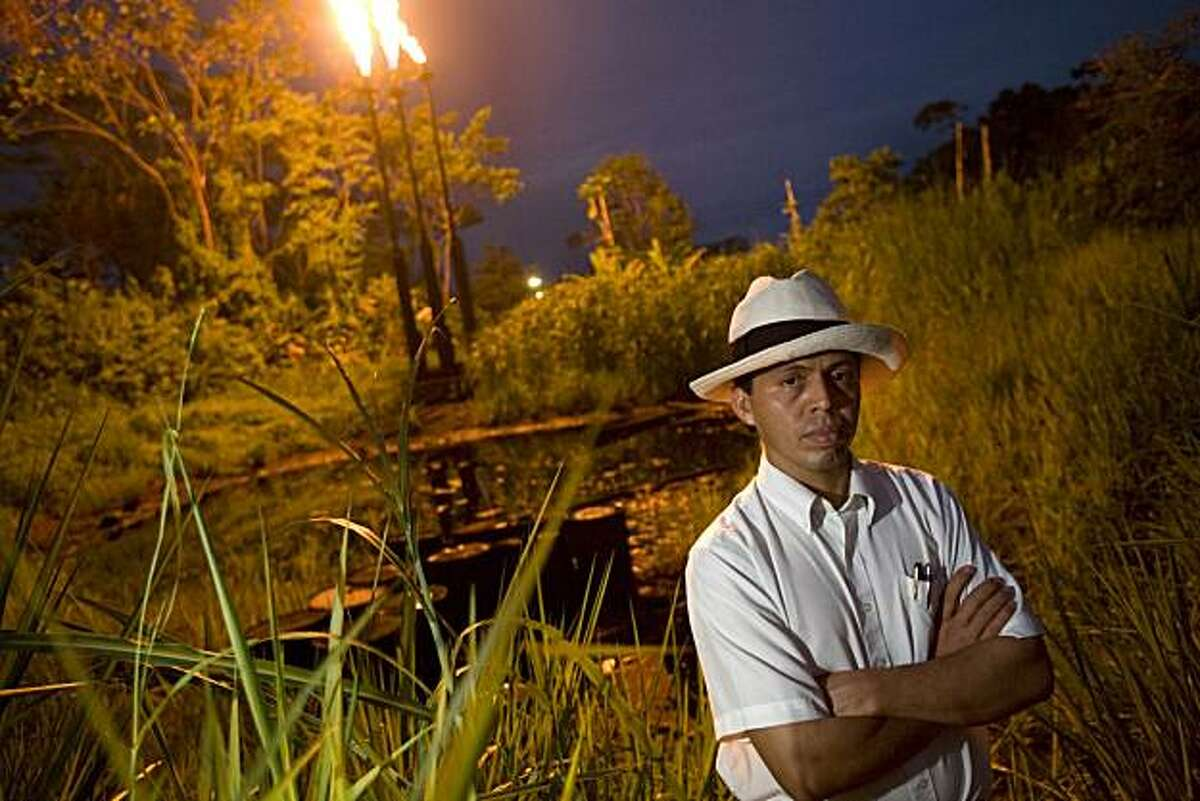 Pablo Fajardo stands in front of a pool of crude oil and waste and two towers that burn natural gas at the station North Lago Agrio in Lago Agrio, Ecuador, on December 17th, 2007. This pool of waste was left by Petro Ecuador, who took over after Texaco. Texaco passed on their bad practices to Petro Ecuador when they left the country. Pablo Fajardo is the lead attorney for the plaintiffs in the lawsuit against Texaco, which is now owned by Chevron. For twenty years Texaco was responsible for recklessly disposing of crude oil and toxic waste which leaked into the water supply of the people living in theses areas. There is now a higher rate of cancer, birth defects, and skin diseases. The 6 billion dollar case has been dragged out for 14 years. Pablo, who grew up in proverty and witnessed first hand the devastation brought to the people and environment because of the reckless behavior of Texaco, works on the case day and night. He just recently won the CNN Hero award in the category of fighting for justice, which has put the spotlight on the case that Chevron is is doing it's best to keep low profile. The six billion dollars that the people of the Ecuadorian jungle are asking of Texaco/Chevron would be used to clean up the the pools of crude oil which are still seeping into the environment. Photo by Ivan Kashinsky / Aurora Photos
