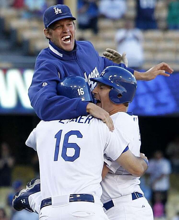 Los Angeles Dodgers' A.J. Ellis, bottom right, celebrates with teammates Andre Ethier, left, and starting pitcher Clayton Kershaw, top, after he hit the game winning single to score Rafael Furcal in the bottom of the 11th inning to give the Dodgers a 7-6victory over the Colorado Rockies in a baseball game, Sunday, Sept. 19, 2010, in Los Angeles. Photo: Danny Moloshok, AP