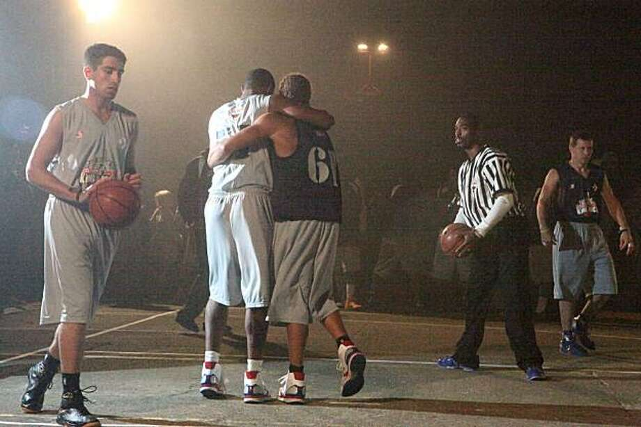 "Nwaluze Umeh from Oakland hugs Will Carrico from San Francisco after beating Carrico in the eerie fogged in first game of Redbull's ""King of the Rock"" one-on-one basketball tournament in the prison yard in San Francisco's Bay on Saturday, September 18, 2010.  Sixty-four players played for the title of ""King of the Rock"" when basketballs hit the courts on ALcatraz for the first time since inmates left the Island nearly 50 years ago. Umeh won the game. Kat Wade / Special to the Chronicle Photo: Kat Wade, Special To The Chronicle"