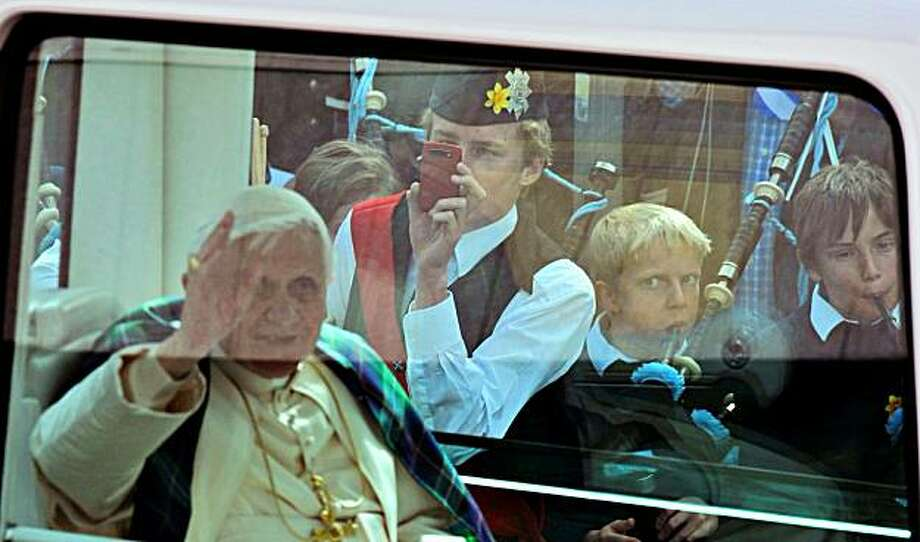 "Pope Benedict XVI waves to to crowds as he is driven by popemobile along Princes Street, in Edingurgh, Scotland on September 16, 2010.   Pope Benedict XVI urged all parties involved in Northern Ireland to work for a ""just and lasting peace"" in his first speech of an historic state visit to Britain on Thursday. Photo: Adrian Dennis, AFP/Getty Images"