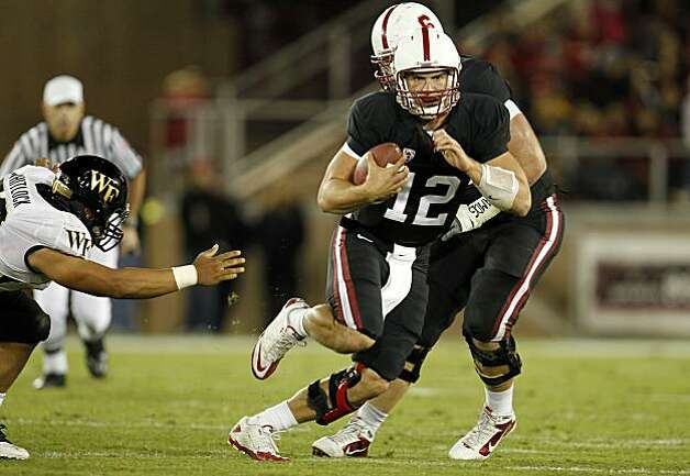 Stanford's quarterback, Andrew Luck, (12) picks his way through the line enroute to a 52 yard touchdown run in the second quarter,as the Stanford Cardinal takes on Wake Forest in college football action at Stanford Stadium in Palo Alto, Ca. on Saturday Sept. 18, 2010. Photo: Michael Macor, The Chronicle