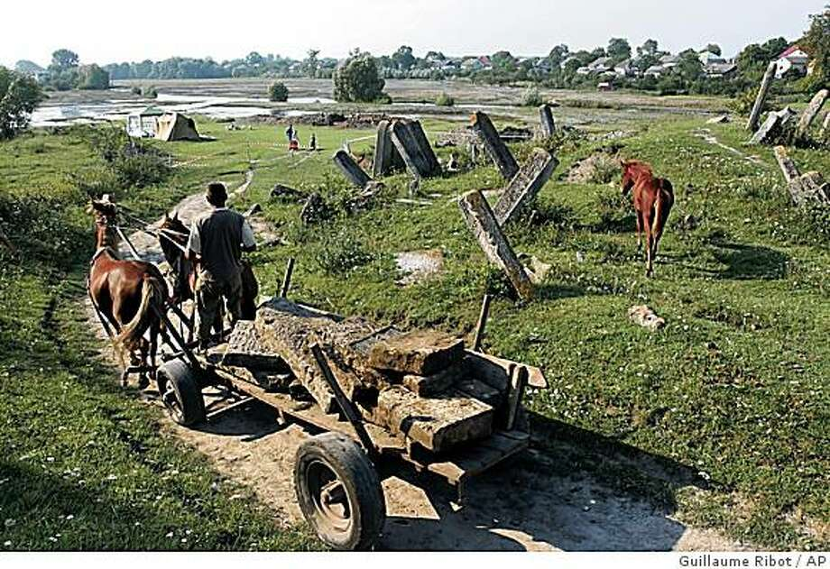 ** ADVANCE FOR SUNDAY, FEB. 1 ** This August 2006 photo released by Yahad-In-Unum and the Museum of Jewish Heritage-A Living Memorial to the Holocaust, shows tombstones, once stolen from a Jewish cemetery and used to build a cattle crossing in Bus'k, Ukraine, being returned to the cemetery. The extermination of over 2 million Eastern European Jews by guns in the middle of quiet villages and towns across Ukraine, Russia and Belarus has been under researched and the victims have been largely forgotten. Many of their remains still lie unidentified and unmarked. (AP Photo/Guillaume Ribot) ** NO SALES ** NO ONLN ** NO IONLN ** Photo: Guillaume Ribot, AP