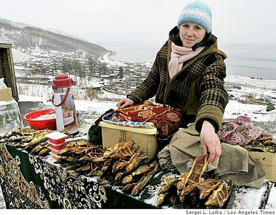 RUSSIA ECOLOGY: A woman offers smoked omul at a roadside stand near Lake Baikal. The world's deepest and oldest fresh-water reserve is treasured by evolutionary biologists as a liquid cornucopia of rare species. Illustrates RUSSIA-ECOLOGY (category i) by Megan K. Stack (c) 2009, Los Angeles Times. Moved Tuesday, Jan. 20, 2009. (MUST CREDIT: Los Angeles Times photo by Sergei L. Loiko.)A woman offers smoked omul at a roadside stand near Lake Baikal. The world's deepest and oldest fresh-water reserve is treasured by evolutionary biologists as a liquid cornucopia of rare species. Illustrates RUSSIA-ECOLOGY (category i) by Megan K. Stack (c) 2009, Los Angeles Times. Moved Tuesday, Jan. 20, 2009. (MUST CREDIT: Los Angeles Times photo by Sergei L. Loiko.) Photo: Sergei L. Loiko, Los Angeles Times