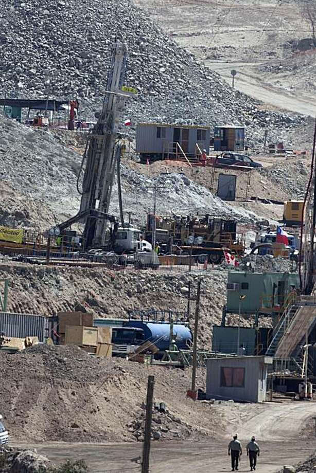 Two policemen walk next to the drill that is being used in the rescue operation of thirty-three miners trapped at the San Jose mine in Copiapo, Chile, Friday, Sept. 17, 2010. Rescuers achieved a key breakthrough in efforts to rescue the miners on Friday, reaching the caverns where they are imprisoned with a bore hole that will now be widened so that they can be pulled to freedom. The miners have been trapped deep underground since the mine collapsed on Aug. 5. (AP Photo/Aliosha Marquez) Photo: Aliosha Marquez Alvear, AP
