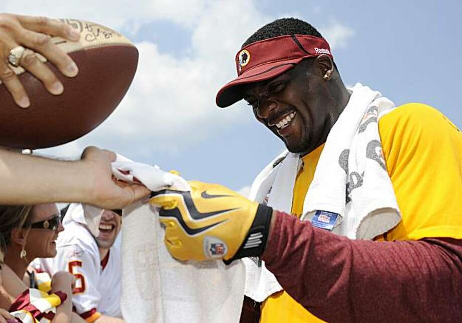 FILE - This Aug. 7, 2010, file photo shows Washington Redskins running back Clinton Portis, right, signing autographs for fans after football practice at the NFL football team's training camp, at Redskins Park in Ashburn, Va.  Thursday, Sept. 16, 2010,  was Clinton Portis' day to explain his inflammatory comments about female reporters. Instead, he decided to have some fun with it. Photo: Nick Wass, AP