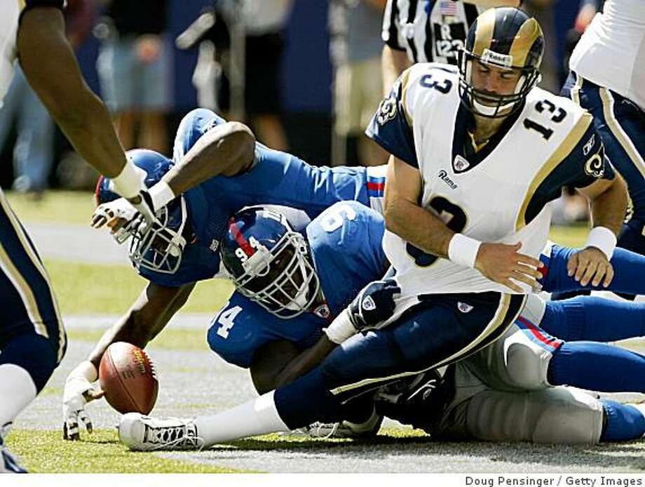 EAST RUTHERFORD, NJ - SEPTEMBER 7:  Defensive end Kenny Holmes #90 of the New York Giants recovers a fumble in the end zone for a touchdown after he and teammate linebacker William Joseph #94 sacked quarterback Kurt Warner #13 of the St. Louis Rams during the game at the Giants Stadium on September 7, 2003 in East Rutherford, New Jersey. The Giants defeated the Rams 23-13.  (Photo by Doug Pensinger/Getty Images) Photo: Doug Pensinger, Getty Images